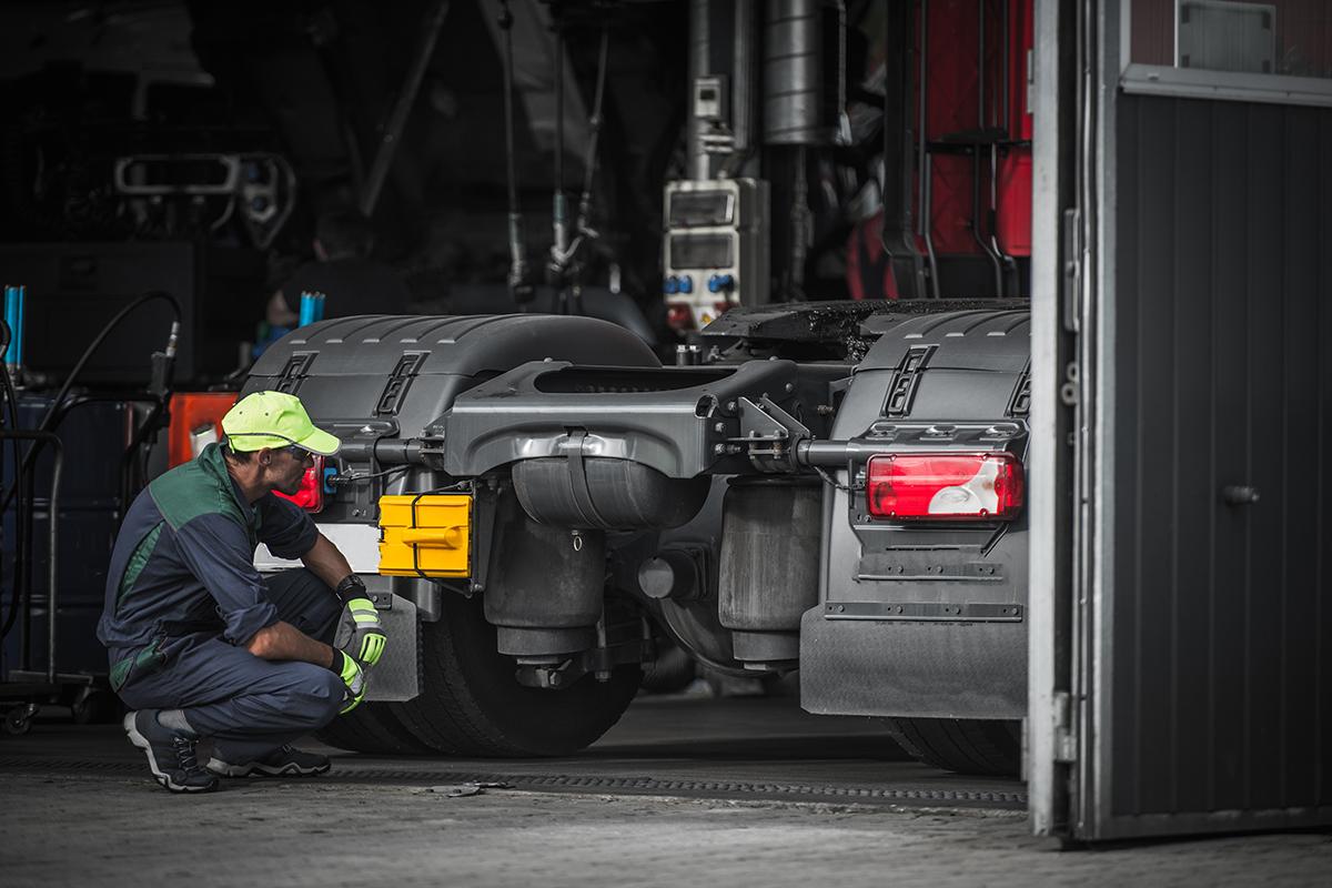 Professional Automotive Caucasian Mechanic Repair Semi Truck Diesel Engine Close Up.
